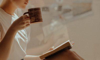 Kvinde drikker te og læser i bog