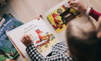 Barn læser i bog med forældre
